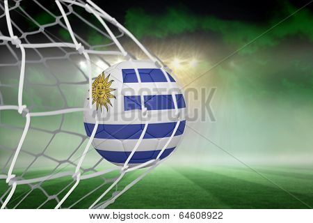 Football in uruguay colours at back of net against football pitch under green sky and spotlights poster