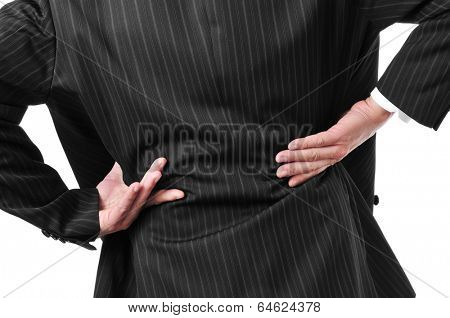 man wearing a suit with his hands in his low back because of his low back pain
