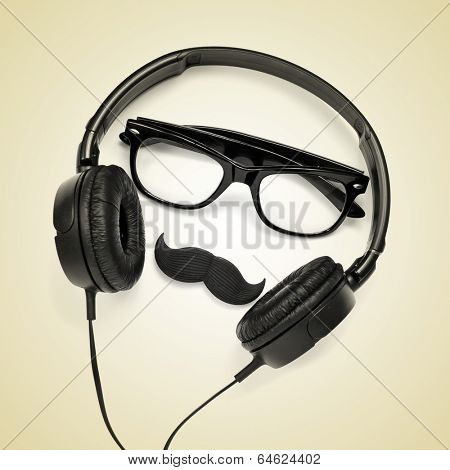 a pair of glasses, a mustache and a pair of headphones on a beige background, depicting a hipster guy