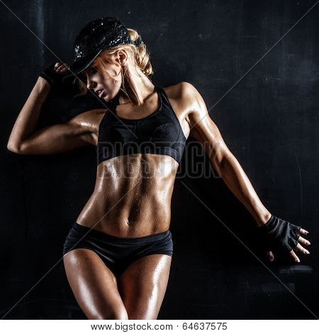 Sexy fit woman in a cap posing on dark background