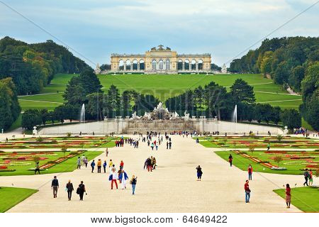 VIENNA, AUSTRIA - SEPTEMBER 26, 2013: Schonbrunn - the summer residence of the Austrian Habsburgs. Area with flower beds regular geometric forms leads to a magnificent building on a green hill