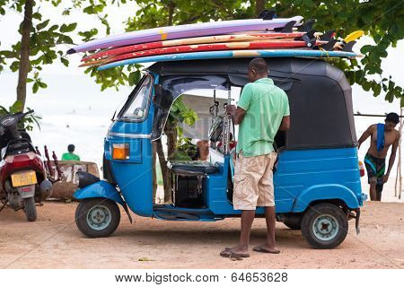 WELIGAMA, SRI LANKA - MARCH 7, 2014: Driver stand in front of blue tuk tuk vehicle transporting surfboards on the roof. Tourism and fishing are two main business in this town.