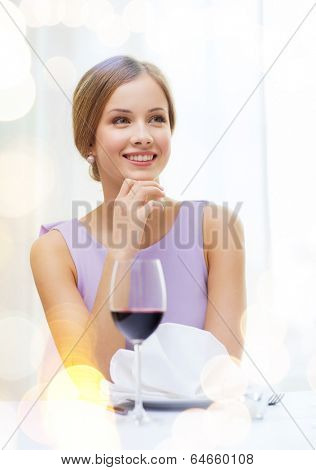 reastaurant and happiness concept - smiling young woman with glass of red whine waiting for date at restaurant poster