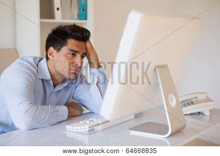 Casual businessman slumped at his desk in his office