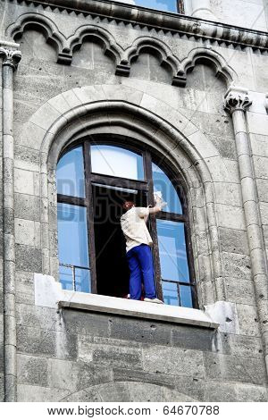 a woman cleans the window and stands dangerously on the windowsill