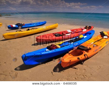 Five Colorful Sea Kayaks Lined Up On Beach