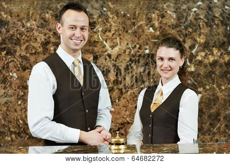 Receptionist or concierge workers standing at hotel counter poster