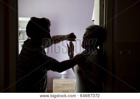 Silhouette of mature couple fighting, the man is physically abusing woman. Woman is victim of domestic violence poster