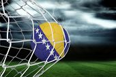 Football in bosnia and herzegovina colours at back of net against football pitch under stormy sky poster