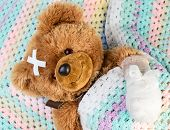 Sick teddy bear with bandage in a bed poster