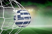 Football in greece colours at back of net against football pitch under green sky and spotlights poster