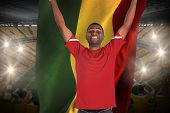 Excited handsome football fan cheering holding ghana flag against vast football stadium with fans in yellow poster