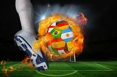 Football player kicking flaming international flag ball against football pitch and goal under spotlights poster