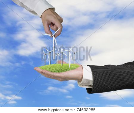 Men Hands Holding Windturbines On Meadow