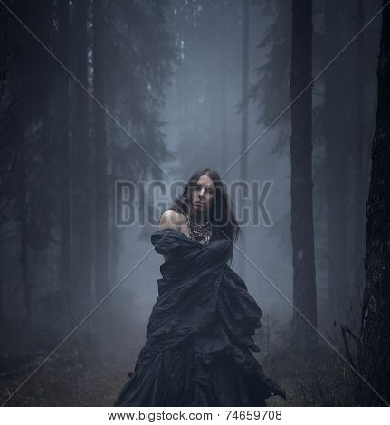 Romantic young man with long hair in the dark forest