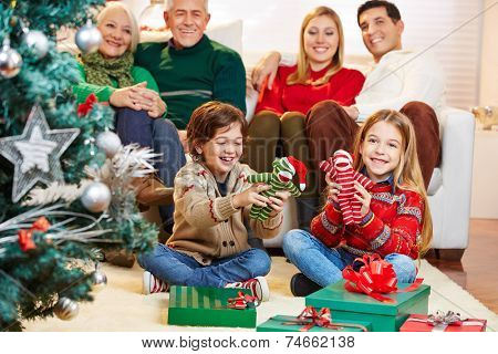 Two children are happy with their gifts at christmas eve with the family