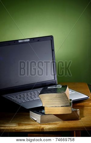 Stack of books and a laptop computer