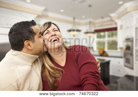 Happy Mixed Race Couple Kissing Inside Beautiful Custom Kitchen.
