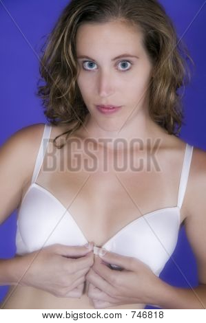 Attractive young woman fastening a plain white bra