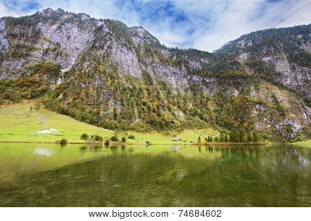 Clouds and mountains reflected in the water. Cloudy day in the Bavarian lake Koenigssee