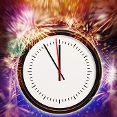 A clock with five minutes before midnight, in background a colorful firework poster