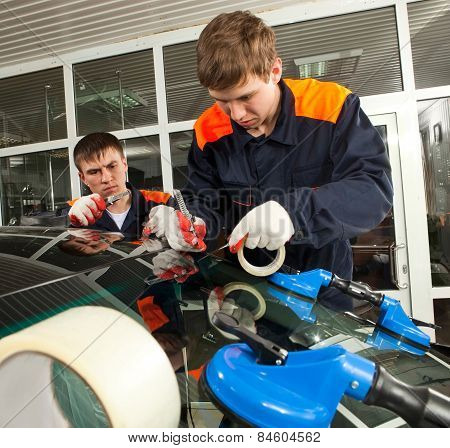 Two Real Mechanics changing the broken windshield of black car in Auto Repair Shop poster