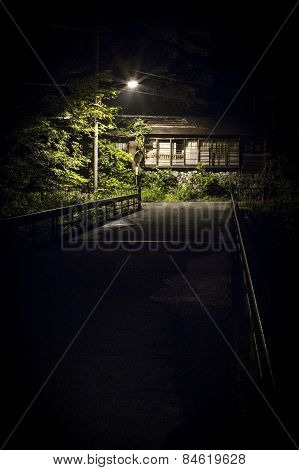 A small abandon house is lit up under a street light