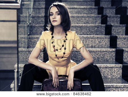 Young fashion business woman sitting on the steps in office interior