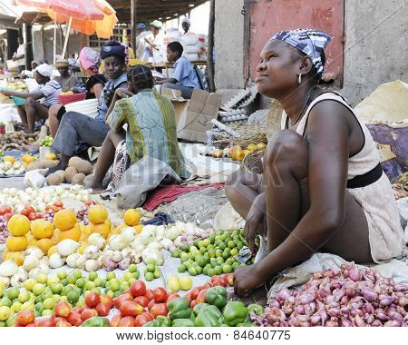 SAINT MARC, HAITI - FEBRUARY 22, 2013:  Women selling fruits and veggies along the street in St. Marc, Haiti.