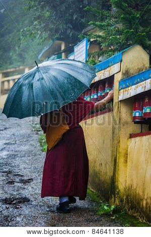 Buddhist monk with umbrella spinning prayer wheels on kora around Tsuglagkhang complex in McLeod Ganj, Himachal Pradesh, India