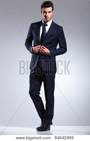 Full body picture of a young business man closing his jacket while looking at the camera.