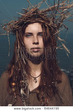 Close up Serious Pretty Young Woman in Boho Fashion with Long Brown Hair Wearing Head Wear Crown of Hay While Looking at the Camera.