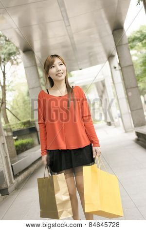 Smile young woman shopping at street in Xinyi district, the business and commercial center in Taipei, Taiwan, Asia.