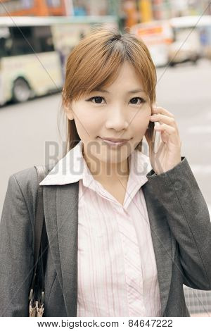 Asian young business woman use cellphone at the street, shot at Xinyi business district, Taipei, Taiwan.