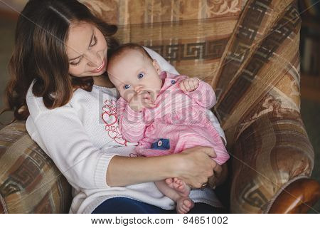 Happy mother with newborn baby girl in her arms.