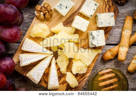 Cheese plate: Camembert cheese blue cheese closeup bread sticks walnuts honey grapes on wooden table poster