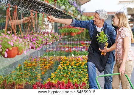 Gardener in front of nursery shop helping woman choosing the right flower