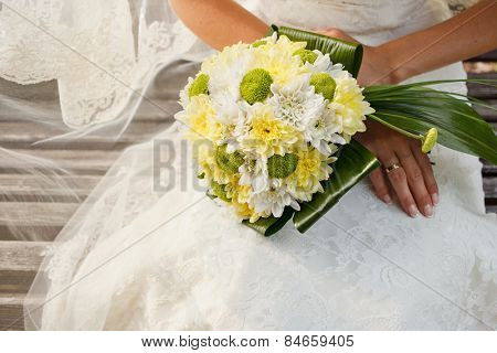 Beautiful wedding bouquet of yellow and green chrysanthemum flowers in hands of the bride