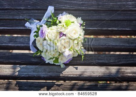 Beautiful wedding bouquet of rose, eustoma and chrysanthemum flowers on on wood boards