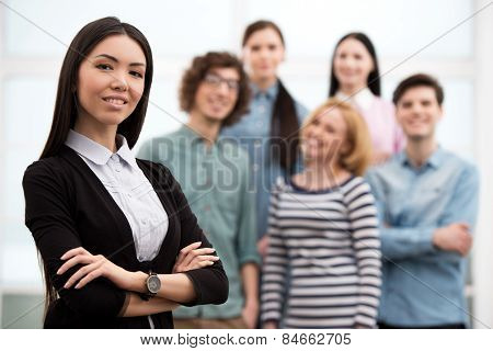 Businesswoman looking at camera with her team on background