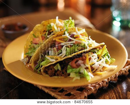 plate of tacos with yellow hard shells and beef