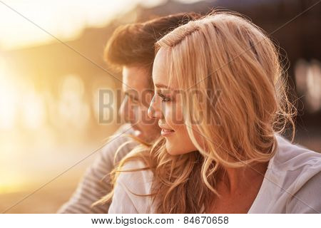 pretty girl cuddling with boyfriend on beach at santa monica with shallow depth of field and bright warm lens flare