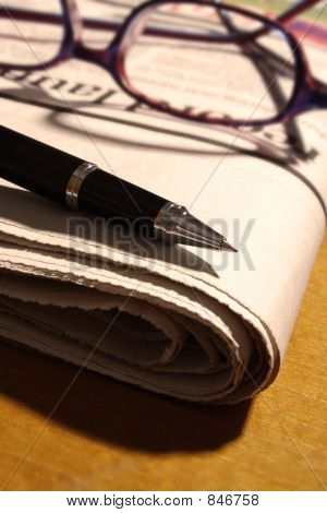 Pen and Glasses on Newspaper