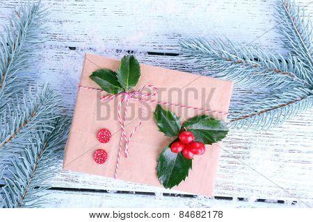 Beautiful Cristmas gift with European Holly (Ilex aquifolium) on wooden background