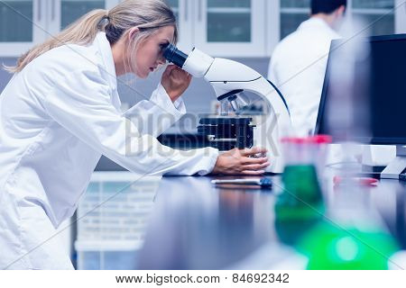 Science student working with microscope in the lab at the university