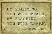 By learning you will teach by teaching you will learn - ancient Latin proverb printed on grunge vintage cardboard poster