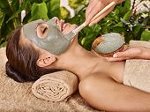 Woman with clay facial mask in beauty spa. In background tropical plants poster