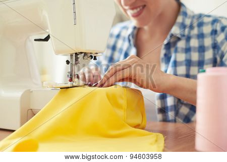 smiley woman sewing on sewing-machine. focus on sewing-machine