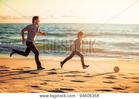Happy father and son play soccer or football on the beach in sunset light