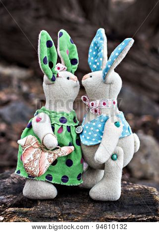 Two toy bunny in love on an old wooden surface
